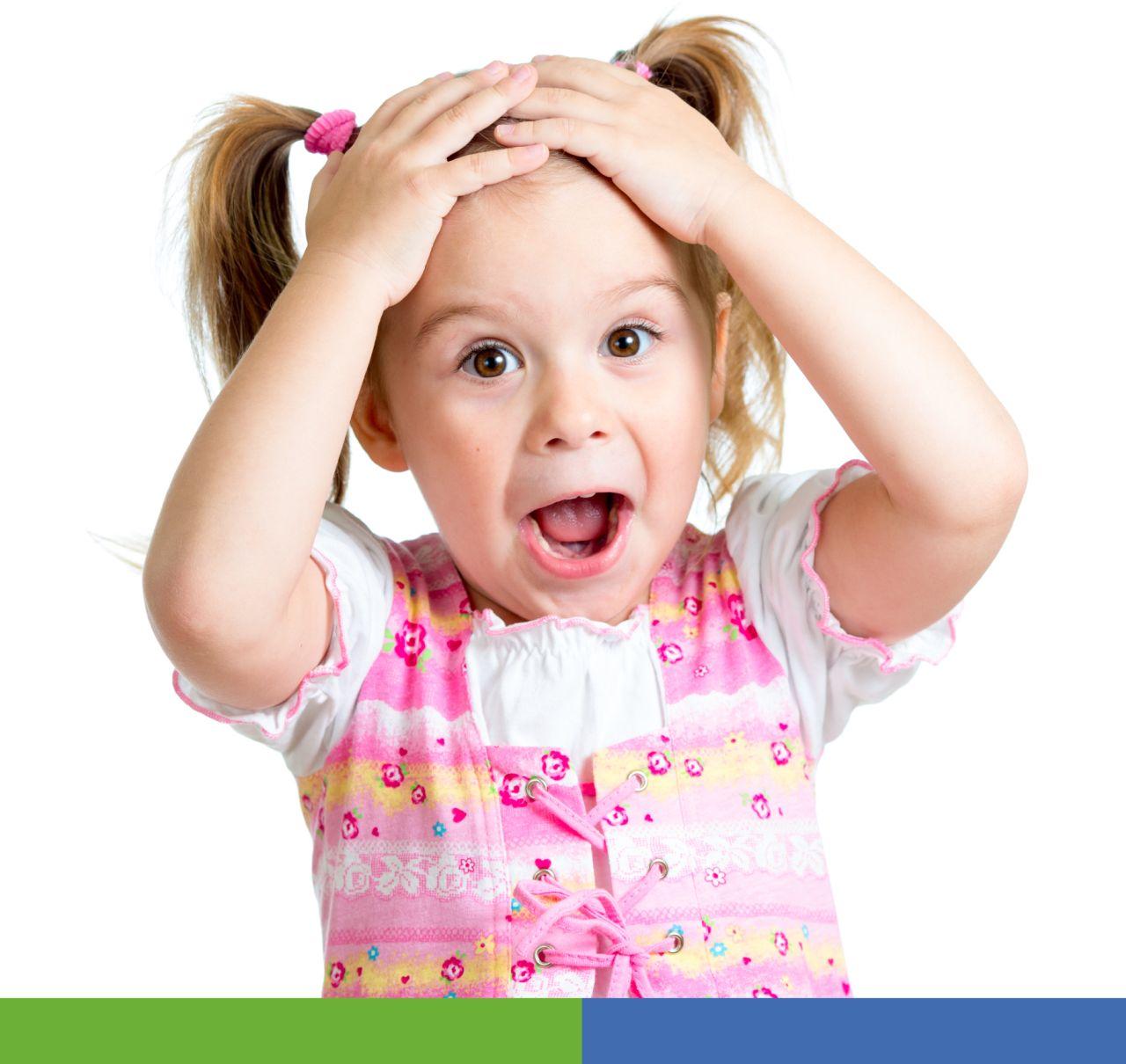 Niña con las manos en la cabeza expresando emoción de alegría.